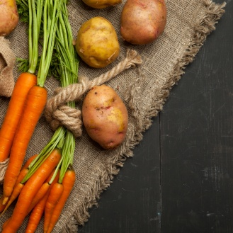 Fresh carrots and potatoes on a black wooden background. rustic style